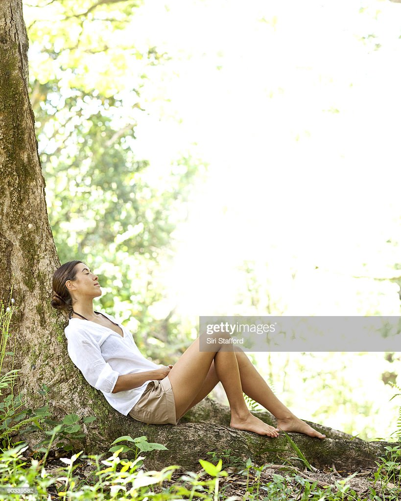 Young woman resting on tree root in forest : Stock Photo
