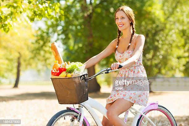 Junge Frau Reiten Fahrrad mit Einkaufstasche voller Lebensmittel.