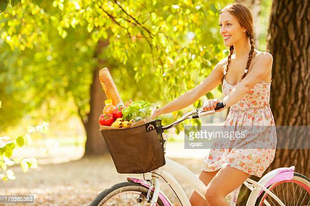 Giovane donna in bicicletta con la borsa della spesa piena di generi alimentari.