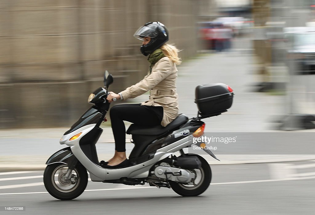 A young woman rides a moped on July 17, 2012 in Berlin, Germany. Mopeds are a common mode of commuter transportation across Europe.