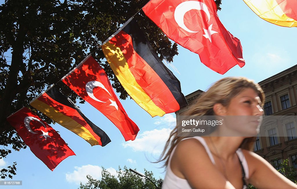 A young woman rides her bicycle past German and Turkish flags fluttering between lamp posts in the immigrantheavy district of Kreuzberg two days...