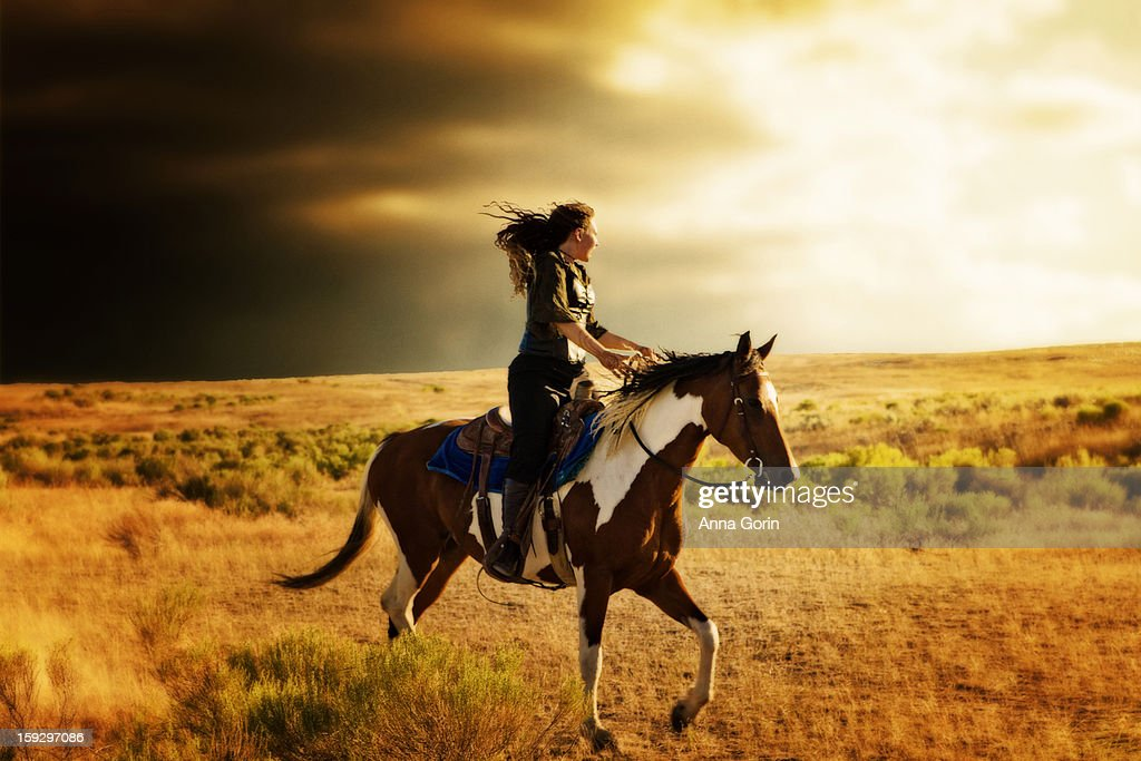 Young woman rides paint horse into storm