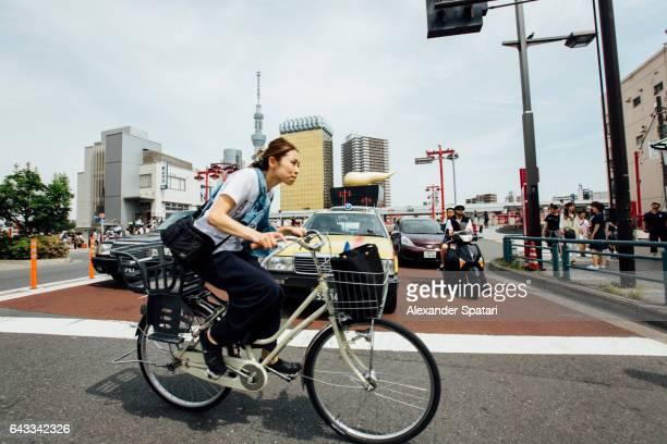 Young woman riding a bike on the streets of Asakusa, Tokyo, Japan
