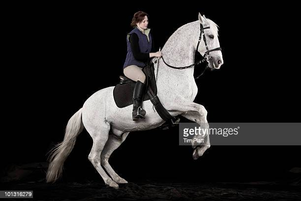 Young woman riding a rearing white horse.