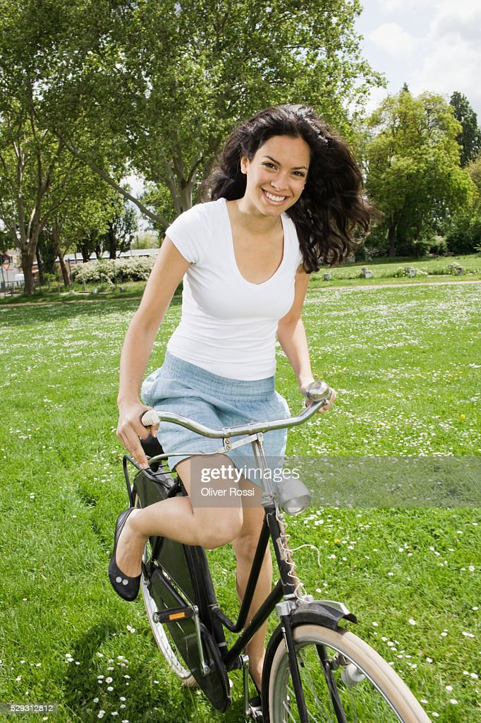 Young woman riding bicycle in grass : ストックフォト