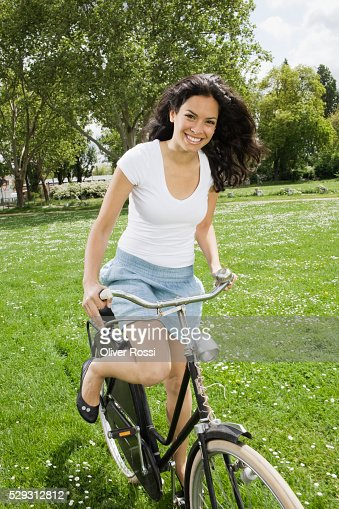 Young woman riding bicycle in grass : Stock Photo