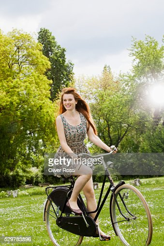 Young woman riding bicycle in grass : Photo