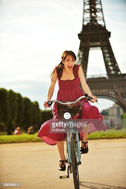 Jeune femme vélo équitation dans le parc de la Tour Eiffel, Paris, France