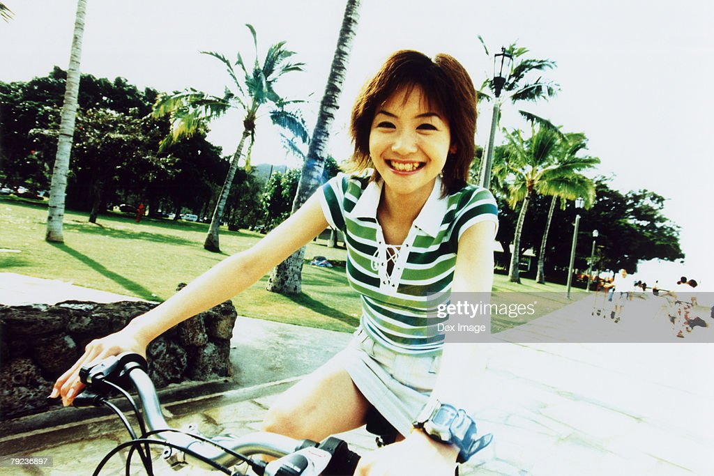 Young woman riding bicycle in the park : Stock Photo