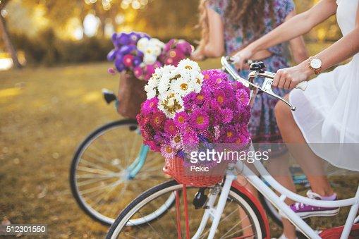 若い女性は彼女の乗馬ホワイトのレトロなヒップスターのサイクリング