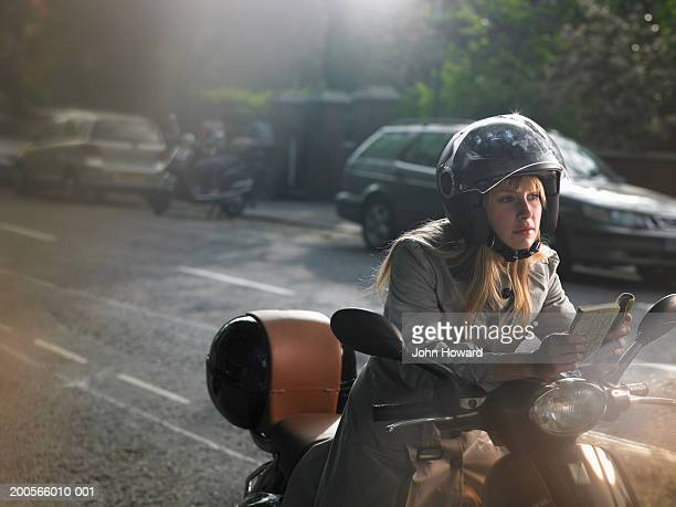 Young woman riding moped