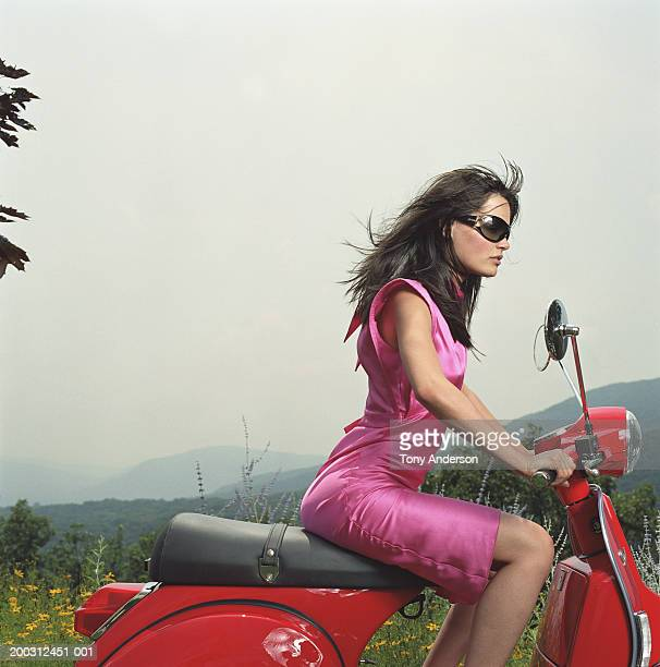 Young woman riding motor scooter, side view