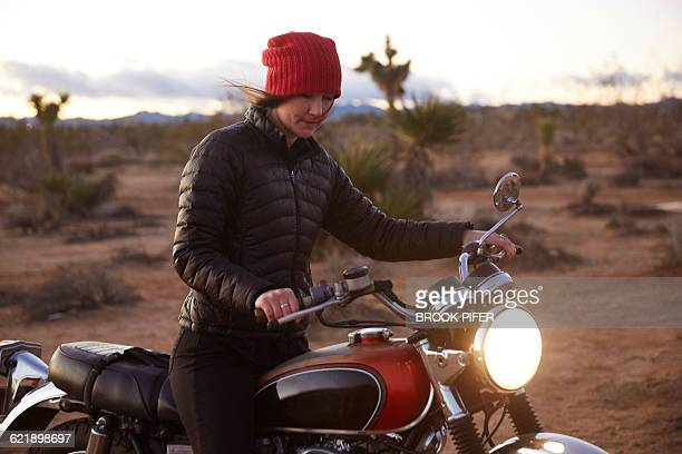 Young woman riding motorcycle on empty road