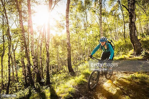 Young woman riding mountain bike through woods, Lake Como, Italy