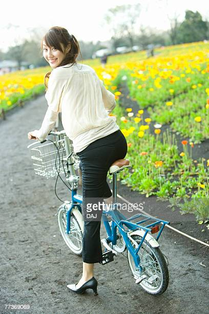 Young Woman Riding on a Bicycle, Rear View, Looking at Camera