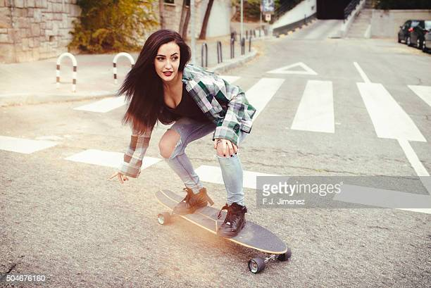 Young woman riding on longboard