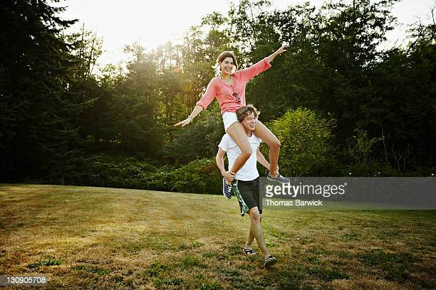Young woman riding on man's shoulders
