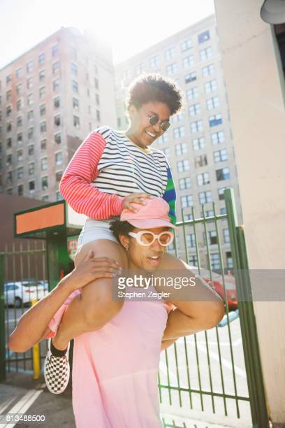Young woman riding on the shoulders of her boyfriend