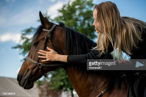 Young woman riding stroking horse