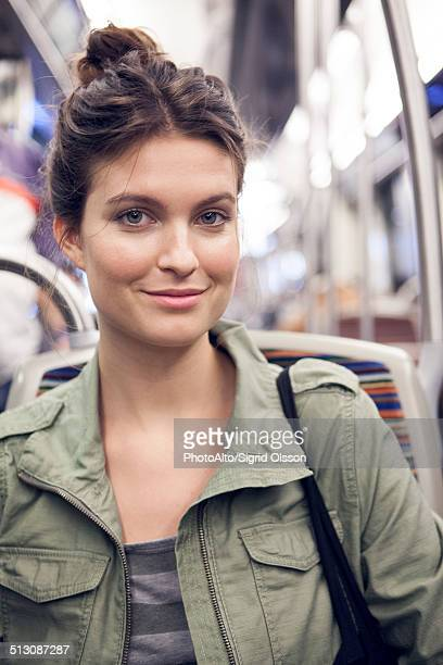 Young woman riding subway train, portrait