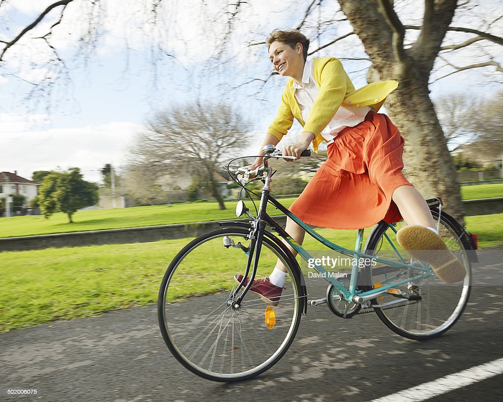 Young woman riding with feet out on a bicycle