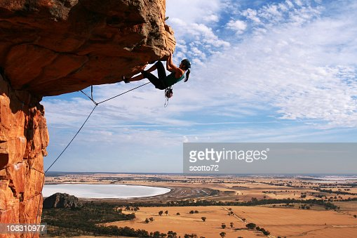 Young woman rock climbing in the desert : Stock Photo