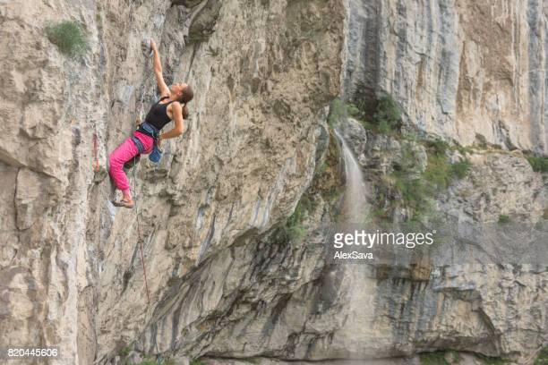 Young woman rock climbing on craggy wall in nature