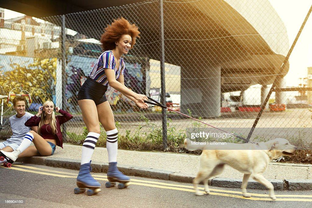 Young woman roller skating with dog : Stock Photo