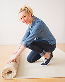 Young woman rolling up carpet, studio shot