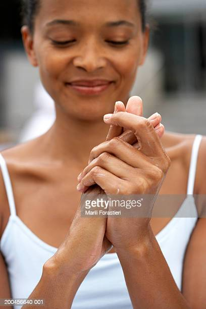 Young woman rubbing lotion on hands, smiling, close-up