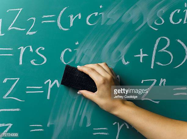 Young woman rubbing out writing on blackboard, close-up of hand