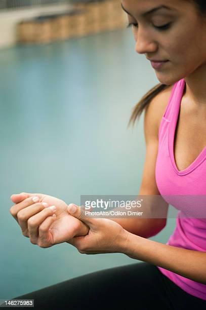 Young woman rubbing wrist