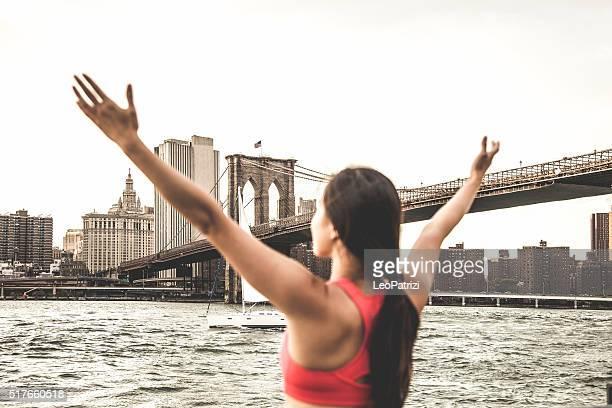 若い女性ランナーを腕を上げる