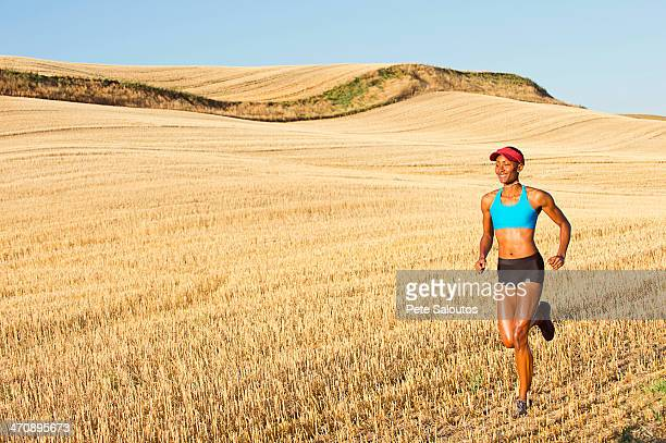 Young woman running across field, Bainbridge Island, Washington State, USA