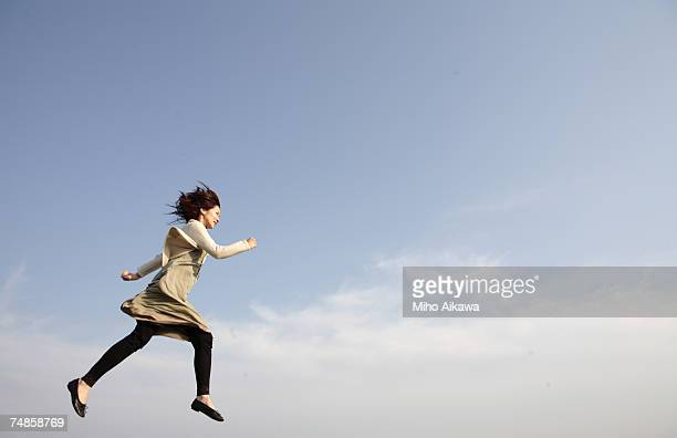 Young woman running against blue sky