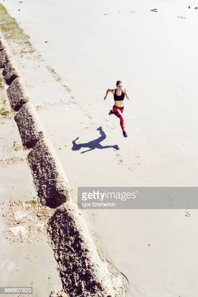 Young woman running along beach, elevated view