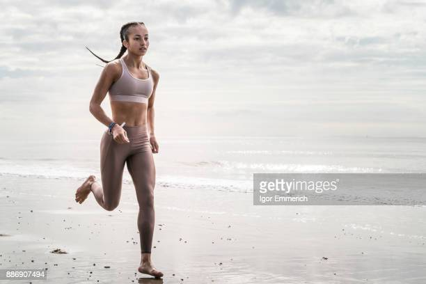 Young woman running along beach