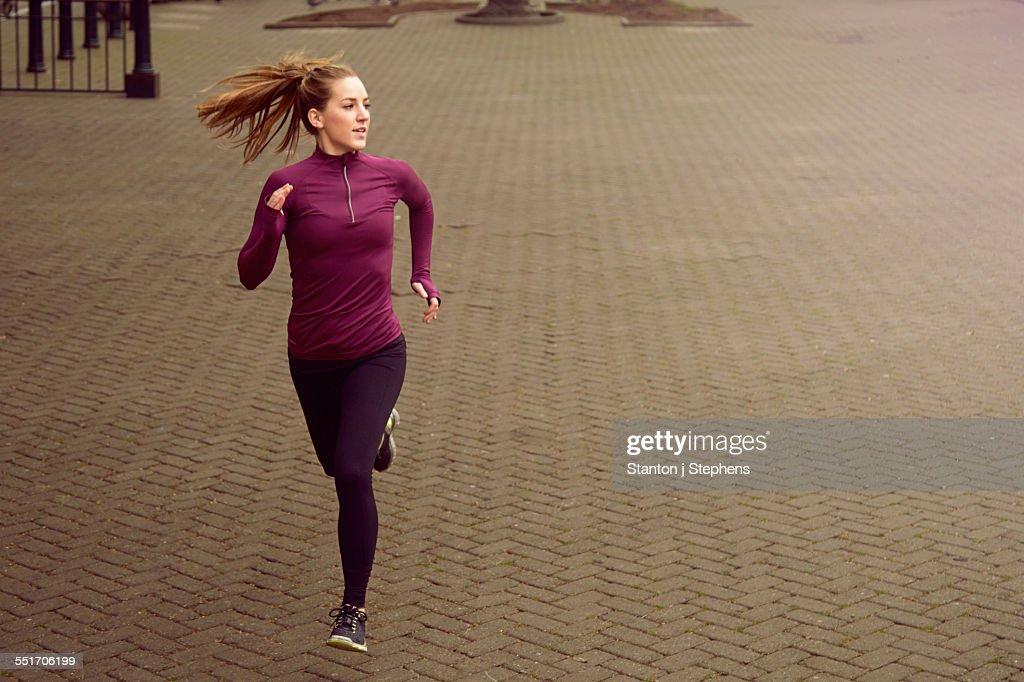 Young woman running along sidewalk : Foto stock