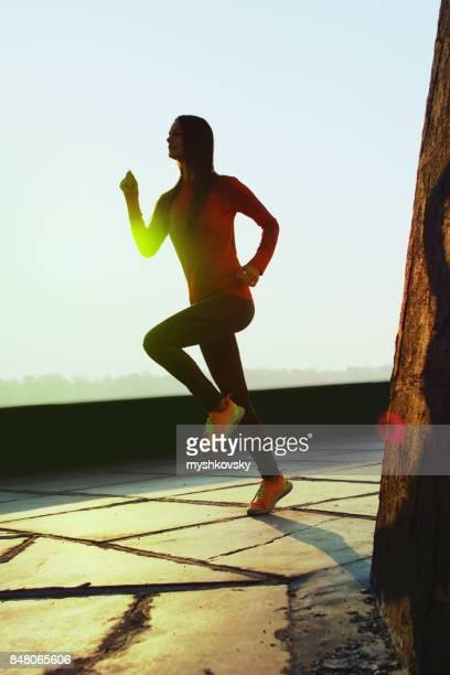 Young woman running along the embankment at dawn