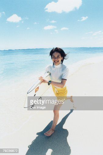 Young woman running at a beach with surfboard : Stock Photo