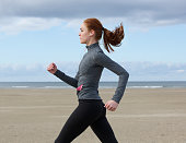 Side view portrait of a young woman running by the beach