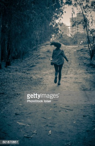Young woman running from danger up dirt track toward apartment blocks