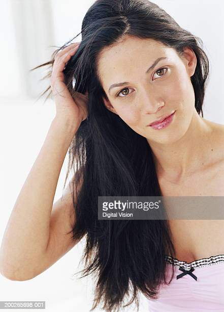 Young woman running hand through hair, smiling, portrait