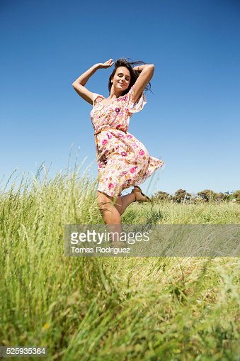 Young woman running in field with arms raised : Photo