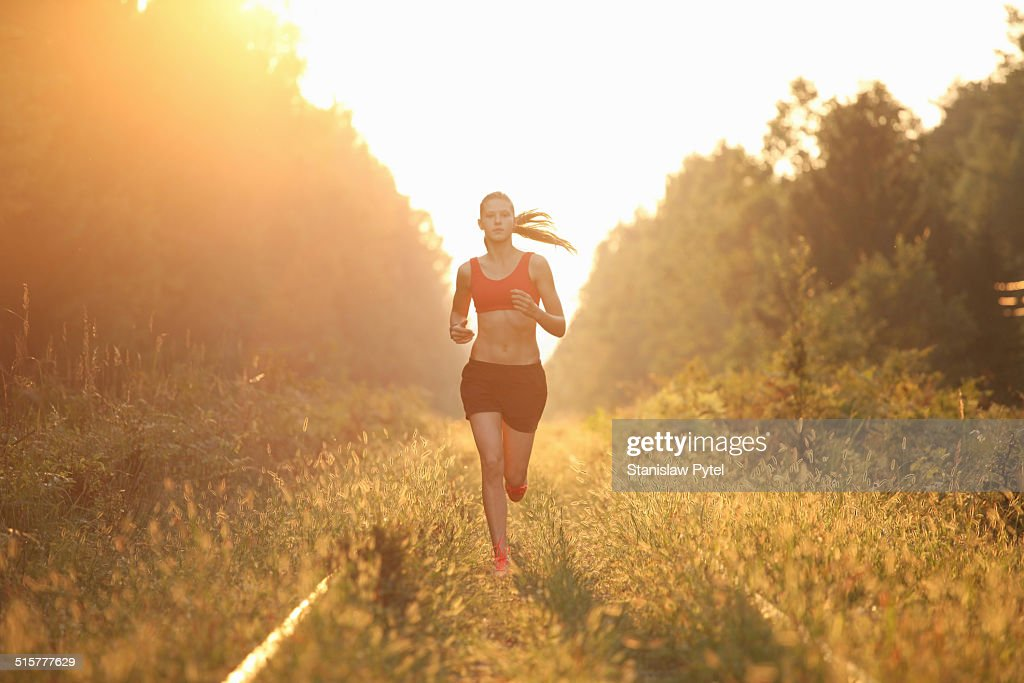 Young woman running in forest : Stock Photo