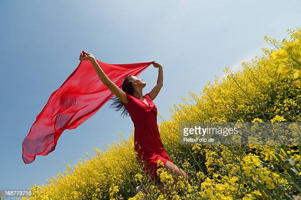 Young woman running in rape holding red scarf to wind