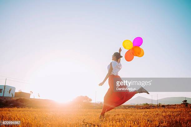 young woman running in the field holding colorful balloons