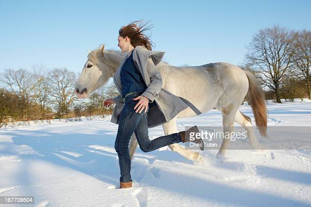Young woman running in the snow with her horse