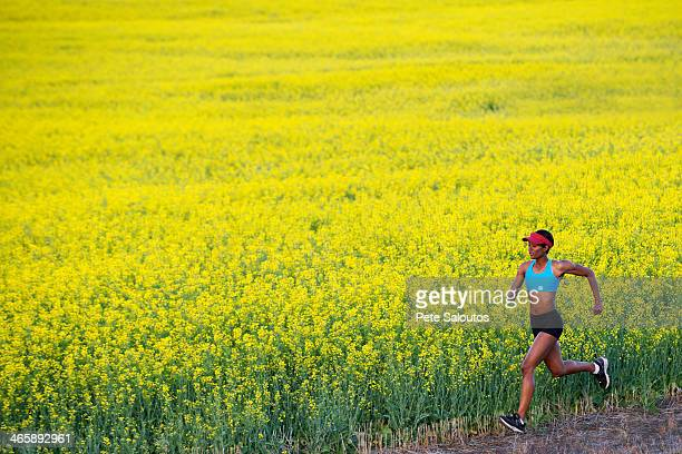 Young woman running next to oil seed rape field