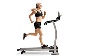 Full length profile shot of a young woman running on a treadmill isolated on white background